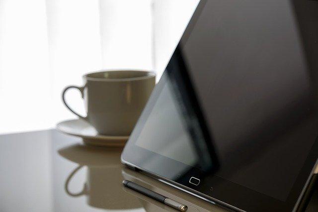Tablet a hrníček kávy